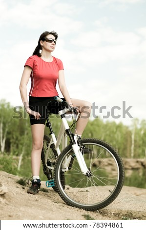 The mature beautiful woman, on bicycle, stand on  beauty nature