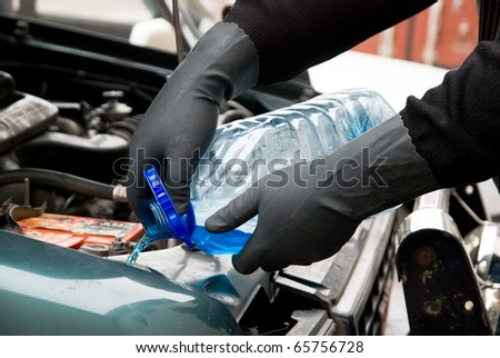 The mechanic fills washing liquid to the car - stock photo