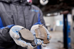 The mechanic holds the old and new brake pads in his hand. Change the old to new brake disc on car in a garage. Auto repair concept.