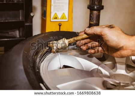 The mechanic's hands in the automobile service center use a heat-resistant grease brush, rubber rim, assembled together to prevent damage and friction between the black tire rim and alloy wheels.  Stock fotó ©