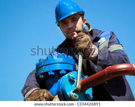 The mechanic - the repairman tightens bolts on a flanged connection of pipeline armature #1334426891