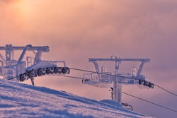 The mechanics of a chairlift at a Swedish ski resort on a cold and colourful winter's day. Low clouds, hard frost and shallow depth of field all add to the drama.