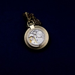 The mechanism of a vintage watch on a black background