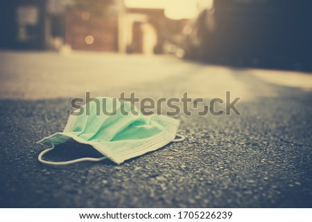 The medical masks used for the anti-corona virus that were used were left on the road. Improper removal of the mask caused Covid-19 to spread in a plastic bag and seal the bag before putting in trash. Foto stock ©