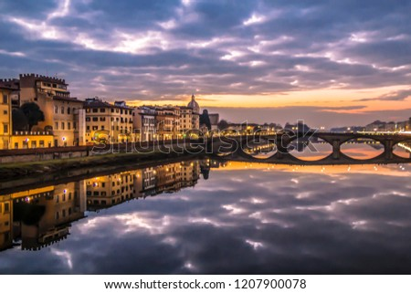 The medieval bridge Carriya on the Arno River, sunset landscape. View of the Arno River from the seafront in Florence