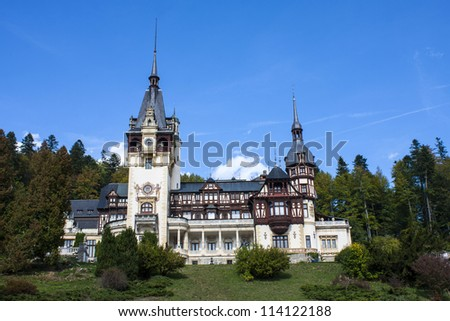 The medieval castle Peles, Sinaia, Romania with towers in gothic style near forest with clear sky