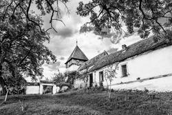The medieval evangelical saxon fortified church of Rodbav village, near Fagaras, Brasov county, Transylvania, Romania; Traditional saxon fortified church of Transylvania in black and white