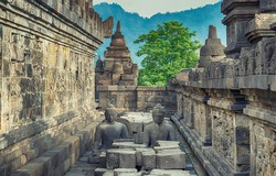 the meditating Buddha statue and stone stupas. Ancient Borobudur Buddhist temple. Great religious architecture. Magelang, Central Java, Indonesia