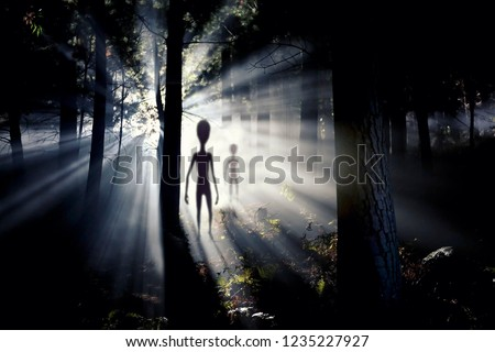 The meeting with an alien civilization - blurred aliens figure and light of an UFO spaceship landing in the forest