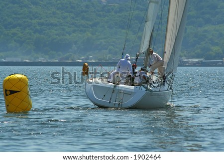 The men work with navigation of a yacht during race. Sailing it is sports for the valid men!