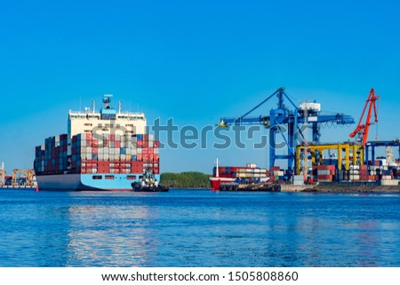 The merchant ship is loaded with colorful containers. The work of the commercial sea port. Cranes in the port perform loading and unloading operations. Landscape of the port in blue. Cargo #1505808860