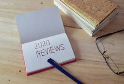The message says 2020 REVIEWS handwritten on notebook laid on wooden table with books, pen and spectacle. Annual performance evaluation concept, selective focus.
