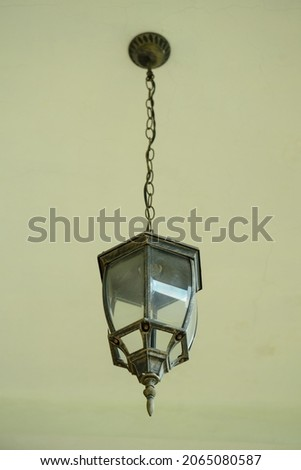 The metal dan glass decorative lamp with white bulb lamp inside the lamp, hanging into the ceilling, isolalated on offwhite colour