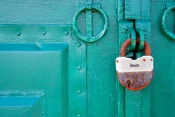 The metal gate is padlocked. Rusty padlock on the gate, close-up. Rough iron doors painted green.