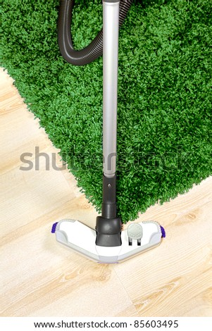 The metal pipe of vacuum cleaner in action -clean a carpet and laminated flooring board.