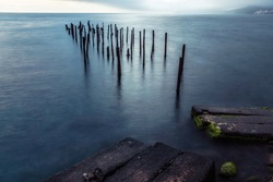 The metal remains of the destroyed pier stick out of sea water near the stone coast. In the distance are blue mountains shrouded in fog. Photo taken at shutter speed.