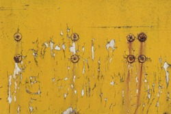 The metal surface, painted with yellow paint, is cracked with age and peeling in places. Rusty steel rivets with rust stains.