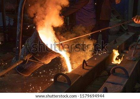 The metal worker is pouring molten metal from melting pot to sand molds. It used when cast irons cannot deliver enough strength. It is a specialized form of casting involving various types of steel. #1579694944