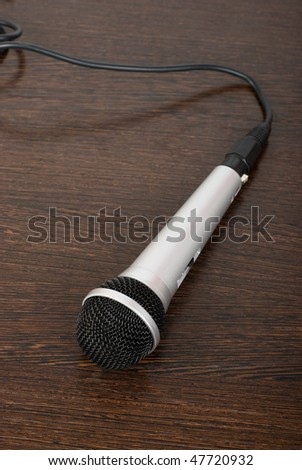 The microphone on a brown wooden background