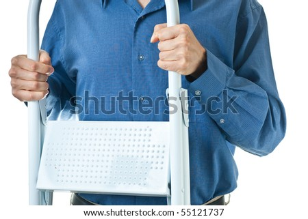 The mid-section of a man in a blue dress shirt, holding a white step ladder, isolated on white.
