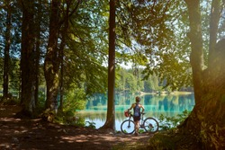 The middle-aged female mountain biker rests in the woods and admires the Alpine lake.