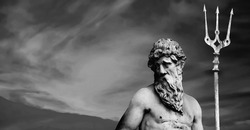 The mighty god of the sea and oceans Neptune (Poseidon). The ancient statue against dramatic view of sky.. Copy space. Black and white image.