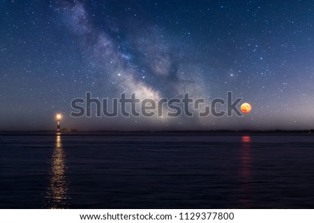 The Milky Way and Full moon in the sky with a Lighthouse beacon reflecting in the water.
