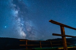 The Milky Way, celestial objects, phenomena and events on a blue, clear and starry night sky captured in a mountainous area with a wooden pontoon in the foreground. Astronomy scientific studies.
