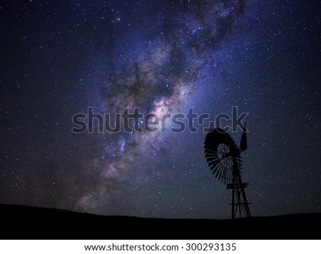 Stock Photo The milky way core rises above a windmill in the Karoo desert, South Africa.