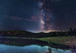 The Milky Way, full of stars, lights up the night sky and reflects in a small fishing lake in the mountains outside of Ruidoso, New Mexico