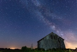 the milky way in the night sky above the abandoned barn