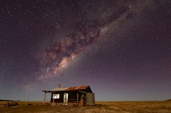 The Milky Way stretches over an abandoned hut in the Australian Outback