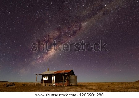 The Milky Way stretches over an abandoned hut in the Australian Outback #1205901280