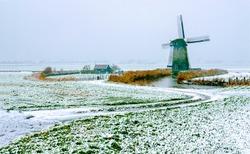 The mill on the farm in winter. Winter wind in windmill farm. Snowy windmill farm in winter