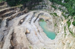 The mine excavation in the photo from the drone. Steep stone walls are slowly overgrown with plants. At the bottom of the quarry there is an azure water tank