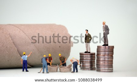 The miniature men who are standing on top of a pile of coins and the miniature men working under it. Concept of labor and economic inequality.