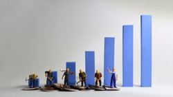 The miniature workers standing on a blue bar graph. Minimum wage increase concept.