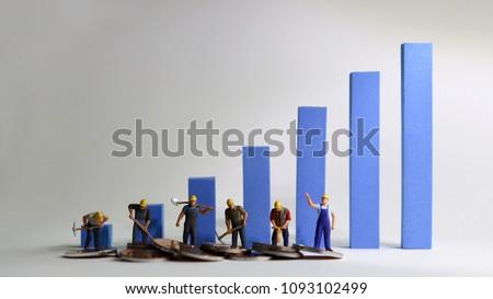 The miniatureworkersstandingonabluebargraph. Minimum wage increase concept. Stock photo ©