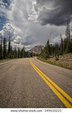 The Mirror lake highway or highway 150 that goes through the Unitas's Mountains in Utah with thunderclouds by Reids Peak/ The Road Home