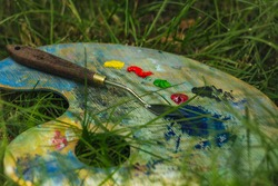 The mixing board lies on the ground on a green lawn in summer. Smeared palette of paints.