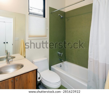 The modern bathrooms are in classic style architecture. Clean contemporary bathroom with green titled bath tub and teak Modern Bathroom vanity.