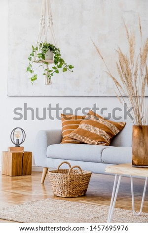The modern boho compostion at living room interior with design gray sofa, wooden coffee table, rattan basket and elegant personal accessories. Honey yellow pillow and plaid. Cozy apartment. Home decor