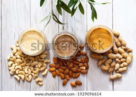 The modern concept of wellness and veganism. Jars of almond, cashew and peanut butter on a white wooden table with an olive branch. Organic, homemade nut butter for a healthy breakfast. Foto stock ©