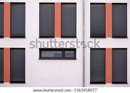The modern facade of a modern residential building with lowered metal blinds and a gutter.