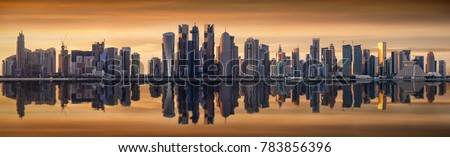 The modern skyline of Doha, Qatar, during a cloudy sunset