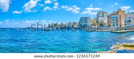 The modern tourist hotels and residential buildings at the shore of St Paul's bay with the fishing harbour on the foreground, Bugibba, Malta