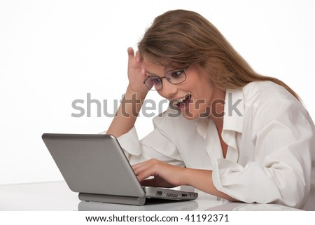 The modern young woman sits at a table with a personal computer, joyfully smiling, looks at the screen of a computer