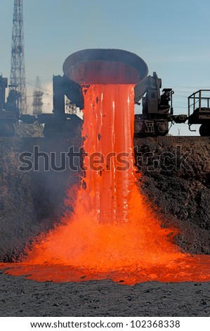 The molten steel is poured into the slag dump. The molten slag is poured from a bucket mounted on a railway platform.