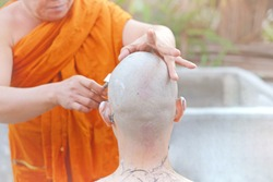 The monk leading the ceremony shaves the heads of the supplicants. The decision of a young man to become a Buddhist monk is  made merit for his family
