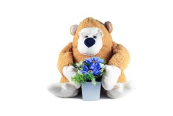 the  monkey doll hold a white pot with purple flowers